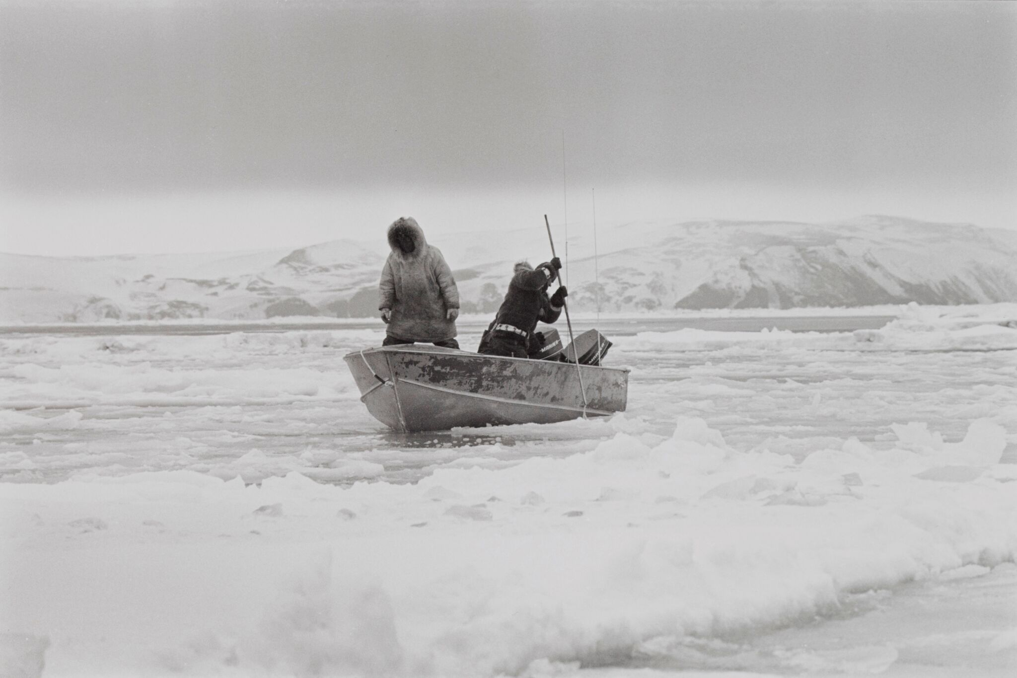 two people in boat spear fishing in icy water