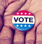 Photo of VOTE pin in open hand